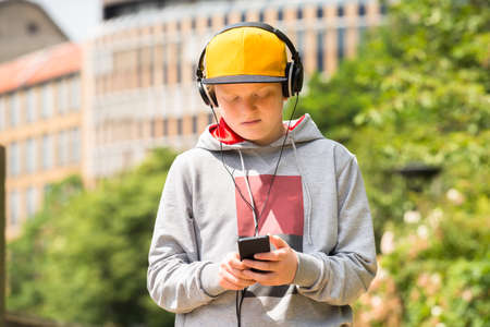 using phone: Boy Wearing Yellow Cap Using Mobile Phone While Listening To Music Stock Photo