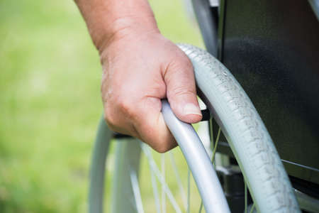 wheelchair access: Close-up Of A Disabled Man Pushing Wheel Of Wheelchair