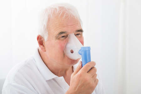 inhaling: Close-up Of A Senior Man Inhaling Through Oxygen Mask In Clinic