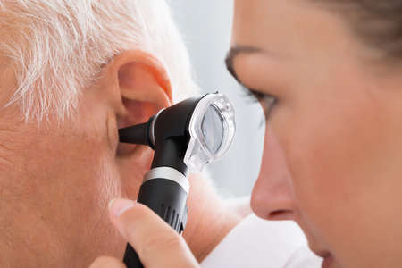 Close-up Of Female Doctor Examining Patients Ear With Otoscope