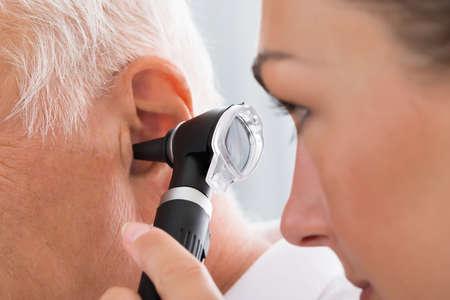 Primo Piano Di Dottoressa Esaminando orecchio del paziente con l'otoscopio Archivio Fotografico