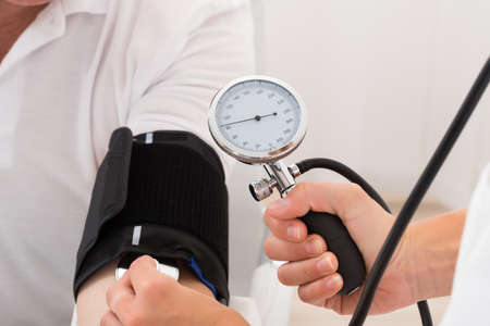 PULSE: Close-up Of A Doctor Checking Blood Pressure Of Patient Stock Photo