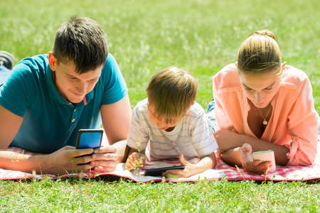 Happy Parents Laying Down In The Park Looking At His Son Using Smartphone