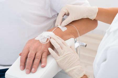 患者さんの手の挿入の点滴と医師の手のクローズ アップ