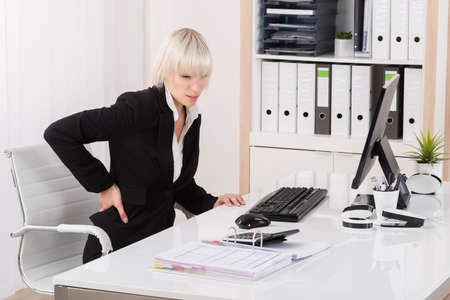 backpain: Young Businesswoman Suffering From Backache In Office