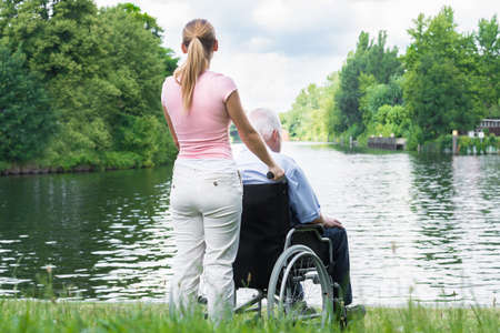 Rear View Of A Young Woman With Her Disabled Father On Wheelchair Looking At Lake Stock Photo