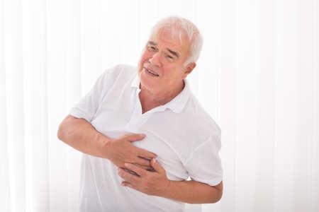 El hombre con la mano en el pecho que sufre de ataque al corazón Foto de archivo