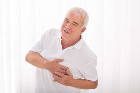 heartbreak issues: Man With Hand On Chest Suffering From Heart Attack Stock Photo
