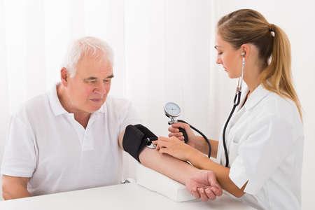 Junger Weiblicher Doktor überprüfen Blutdruck des älteren männlichen Patienten in Klinik