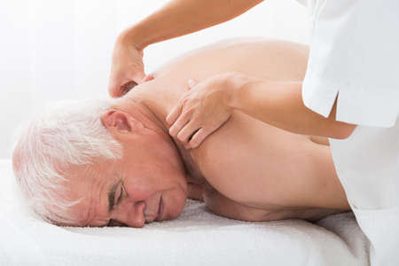 receiving: Close-up Of A Senior Man Receiving Back Massage In Spa Stock Photo