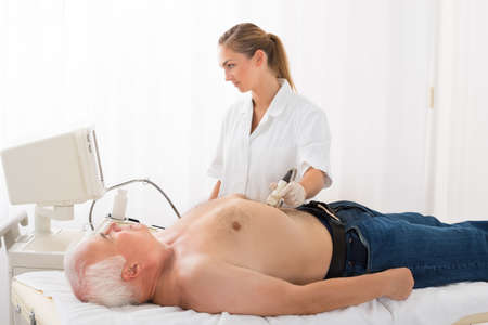 Young Female Doctor Using Ultrasound Scan On Abdomen Of Senior Male Patient In Clinic Stock Photo