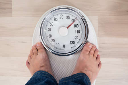 low scale: Low Section Of A Person Standing On Weighing Scale