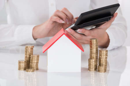 Close-up da mão da fêmea usando a calculadora com modelo da casa e moedas empilhadas na mesa Imagens