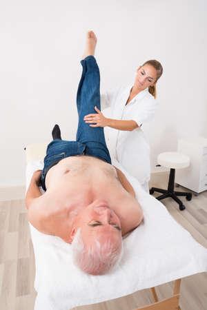 Young Female Masseur Leg Massage To Senior Man