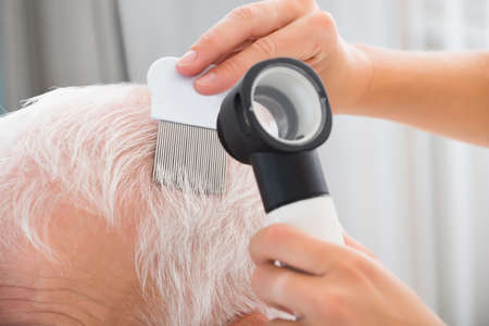 Close-up Of Doctor With Comb And Dermatoscope Doing Treatment Of Senior Patients Hair