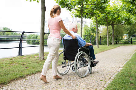 paralysis: Side View Of A Smiling Young Woman Assisting Her Disabled Father On Wheelchair In Park