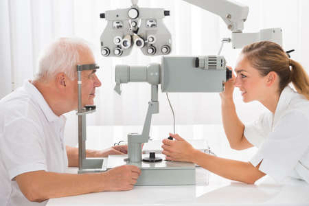 examen de la vista: La hembra joven feliz que realizan pruebas con optometrista Visión Para Paciente Varón mayor
