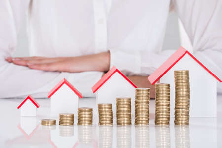 Close-up Of Businesswoman In Front Of Stacked Coins And House Models On Desk