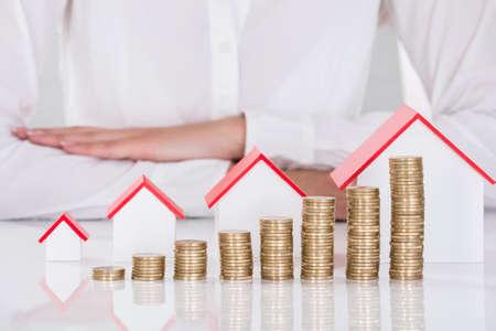 Close-up Geschäftsfrau vor gestapelten Münzen und Haus-Modelle auf Schreibtisch Standard-Bild