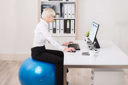 gantt: Young Businesswoman Sitting On Fitness Ball Looking At Gantt Chart On Computer