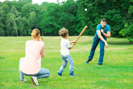 Happy Young Family Playing Baseball At Park Stock Photo