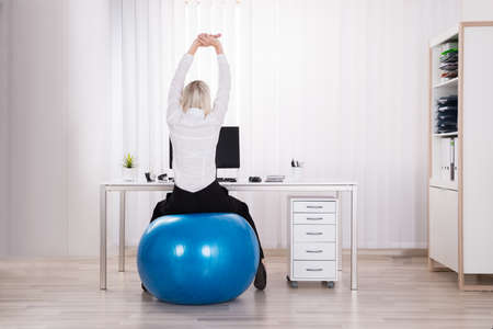 fit ball: Rear View Of Businesswoman Sitting On Fitness Ball Stretching Her Arms In Office Stock Photo
