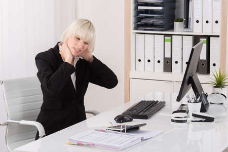 executive woman: Young Businesswoman Suffering From Neckache At Desk In Office