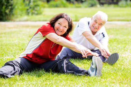 Smiling Senior Couple Doing Fitness Exercise In Park Stock Photo