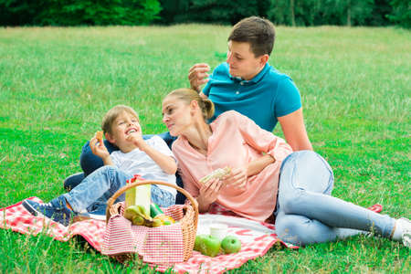 Young Happy Family Enjoying Breakfast At Picnic In The Park