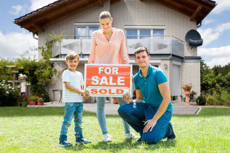 front house: Portrait Of Happy Young Family With A Sale Sign Outside Their Home Stock Photo