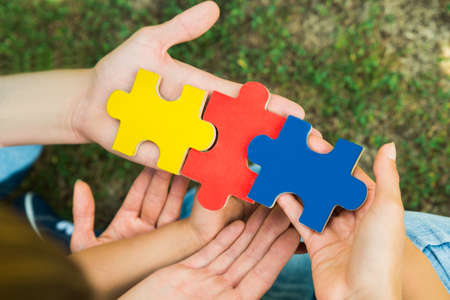 Close-up Of Hands Holding Three Colorful Jigsaw Puzzle Pieces