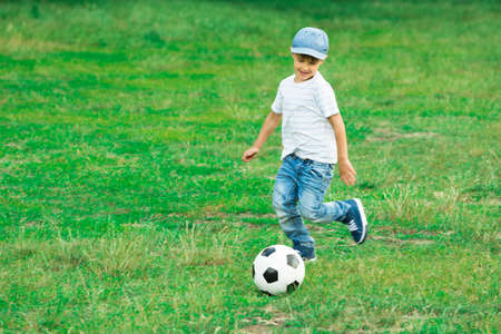 football play: Happy Boy Playing With Soccer Ball In The Park