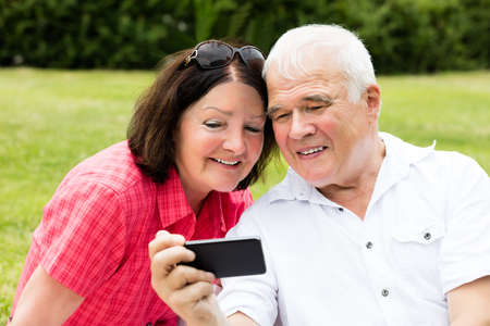 Happy Senior Couple Taking Selfie With Mobile Phone