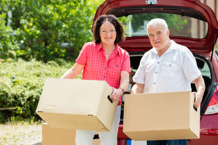 Happy Senior Couple Standing In Front Of Car Holding Cardboard Box