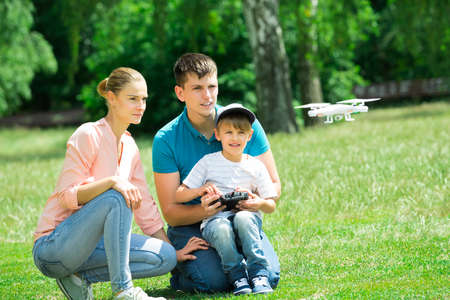 A Boy Operating The Drone By Remote Control With His Parents In The Park