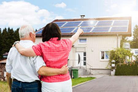 Rear View Of Senior Couple Pointing Finger In Front Of House Standard-Bild