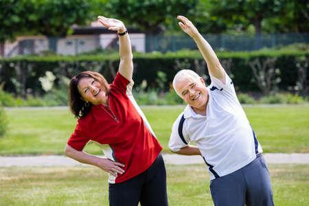 hombres haciendo ejercicio: Activa Pareja mayor que hace hacer ejercicio en el parque A la mañana