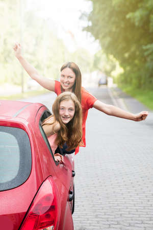 Happy Mother And Daughter Raising Her Arms While Going For A Ride In Red Car