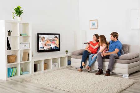 mujer viendo tv: Familia que se sienta en un sofá viendo la televisión en casa