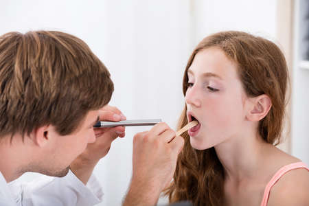 Close-up Of Doctor Examining Girls Throat With Tongue Depressor Stock Photo