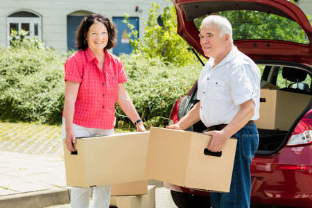 outside house: Happy Senior Couple Standing In Front Of Car Holding Cardboard Box
