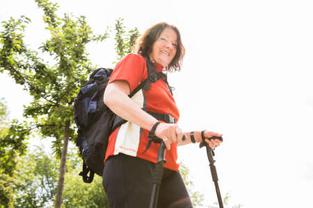 Portrait Of A Happy Senior Female Hiker With Hiking Pole Stock Photo