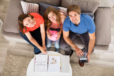 High Angle View Of A Smiling Family Calculating Tax