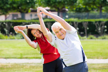 woman stretching: Photo Of Senior Couple Exercising Together At Park Stock Photo