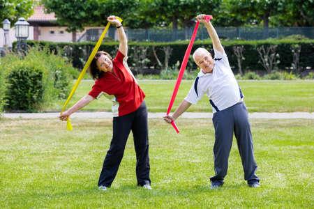 stretch: Happy Senior Couple Exercising With Yoga Belt In Park Stock Photo