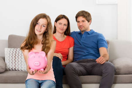 coinbank: Girl Holding Piggybank In Front Of Her Parent Sitting On Sofa Stock Photo