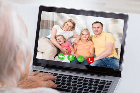 conferencing: Close-up Of Grandmother Video Conferencing With Her Family On Laptop At Home Stock Photo