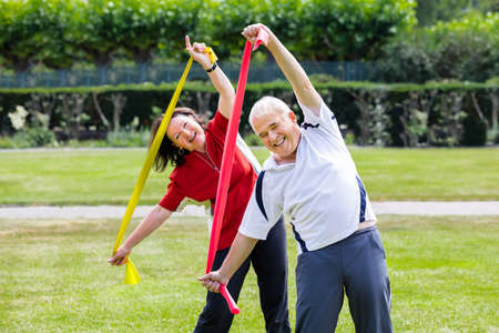 Happy Senior Couple Exercising With Yoga Belt In Park Stock Photo