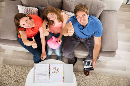 High Angle View Of A Happy Family Sitting On Sofa Gesturing Thumbs Up
