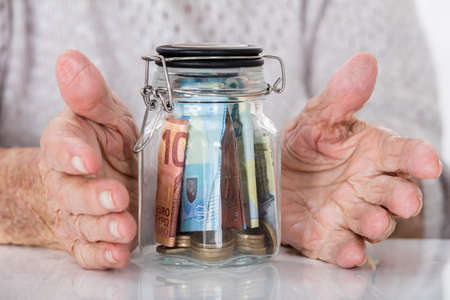 invest: Close-up Of Senior Womans Hand Protecting Glass Jar Of Money